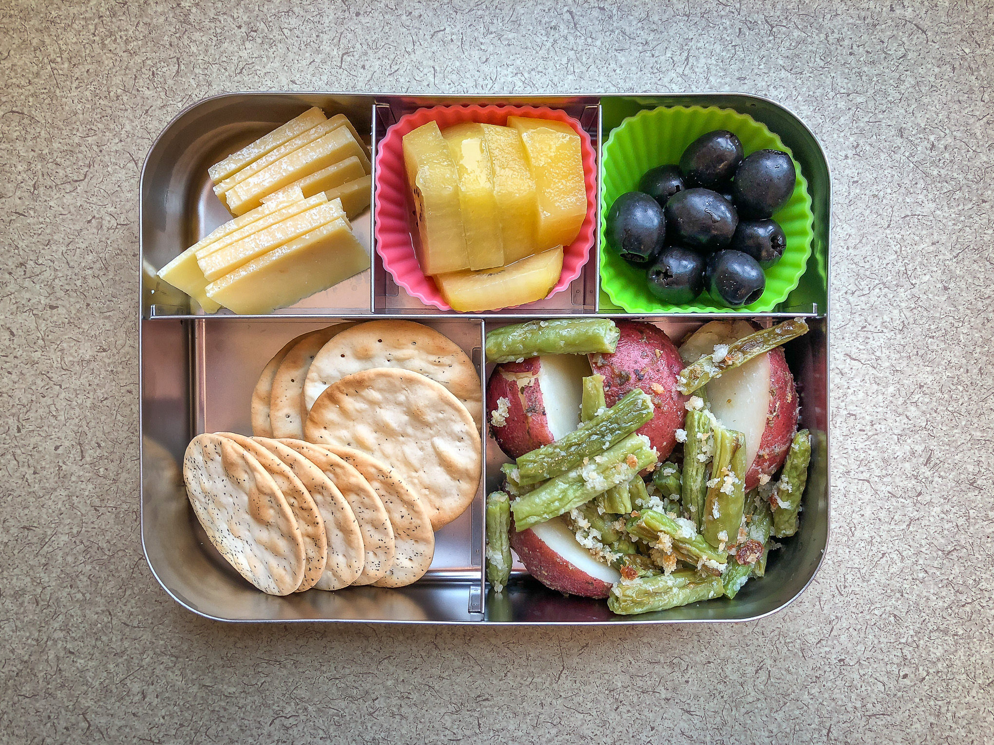 Bento box filled with cheese, fruit and vegetables
