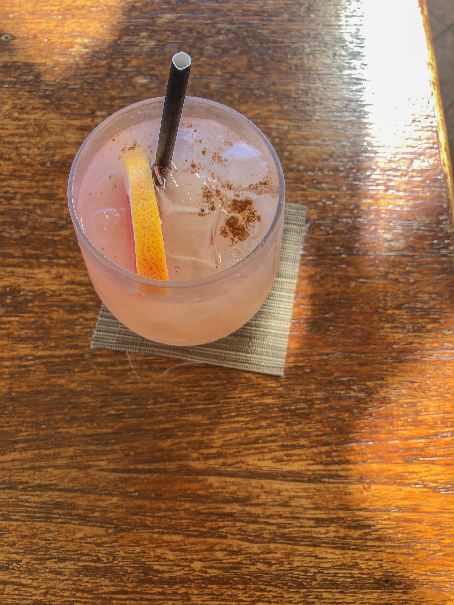 Tropical grapefruit drink in glass with straw and garnish