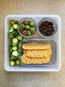 Tupperware filled with kiwi berries, chocolate almonds, parmesan crisps and cucumbers