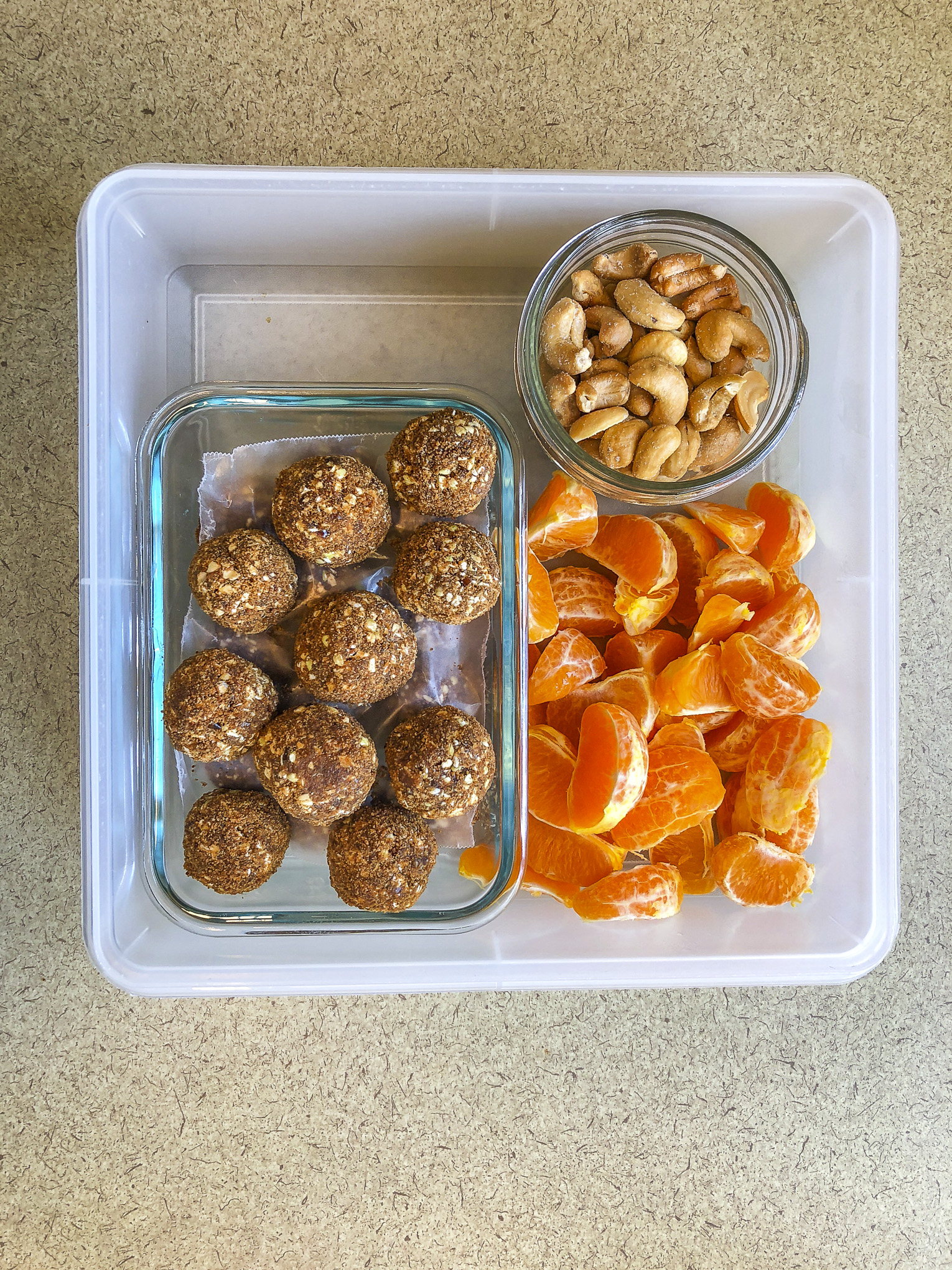 Tupperware filled with cashews, orange segments, and gingerbread bites