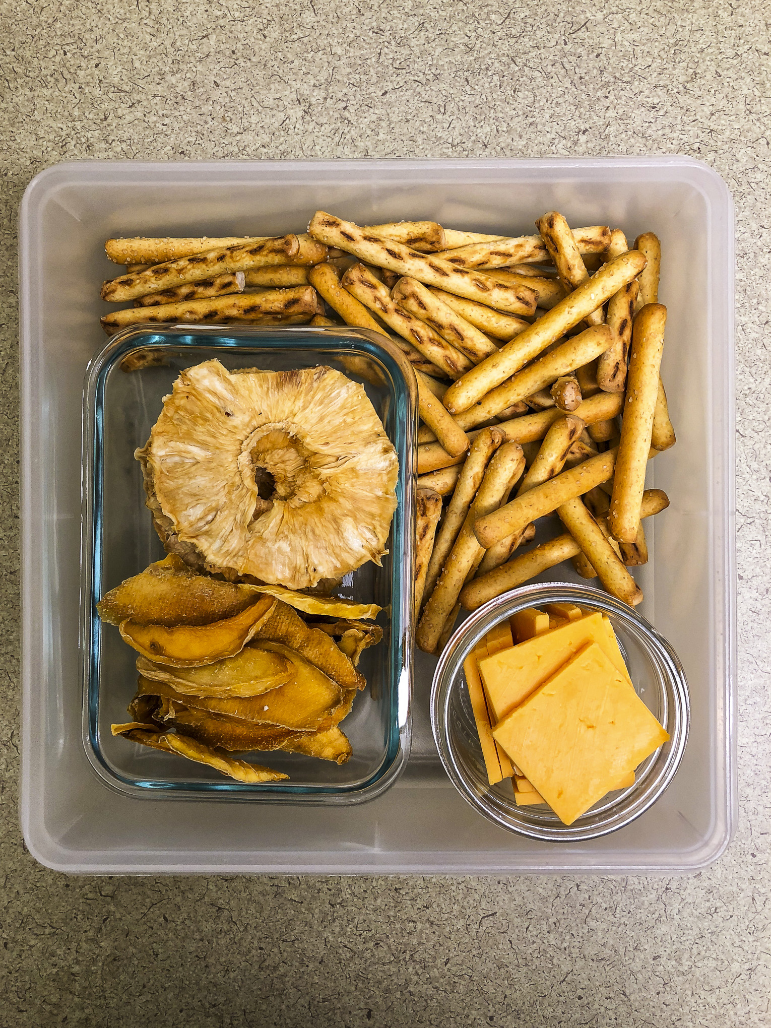 Tupperware filled with pretzels, cheese, dried pineapple and dried mango