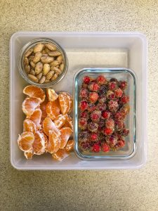 Tupperware filled with candied cranberries, almonds, and orange segments
