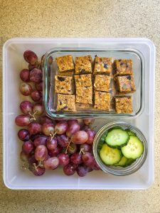 Tupperware filled with granola bars, cucumbers and grapes