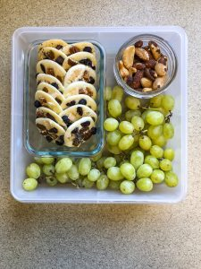 Tupperware filled with white chocolate, nuts and green grapes