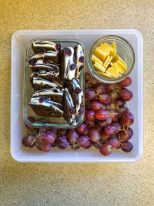 Tupperware filled with gingerbread, cheese and grapes