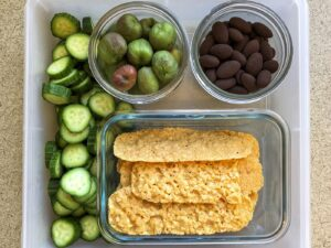 Tupperware filled with cucumbers, kiwi berries and cheese sticks