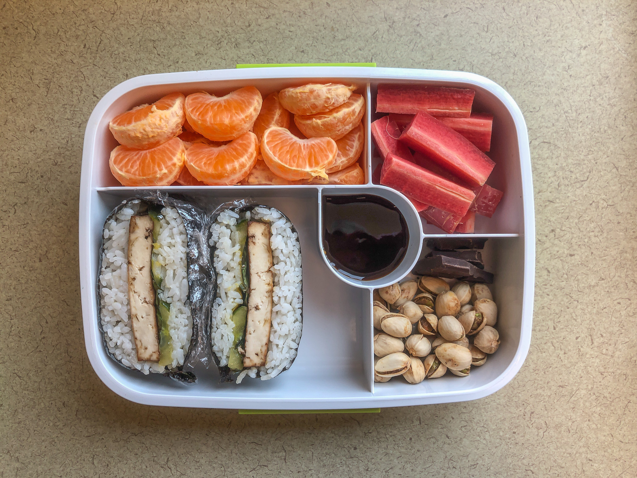 Bento box filled with sushi sandwiches and fruit