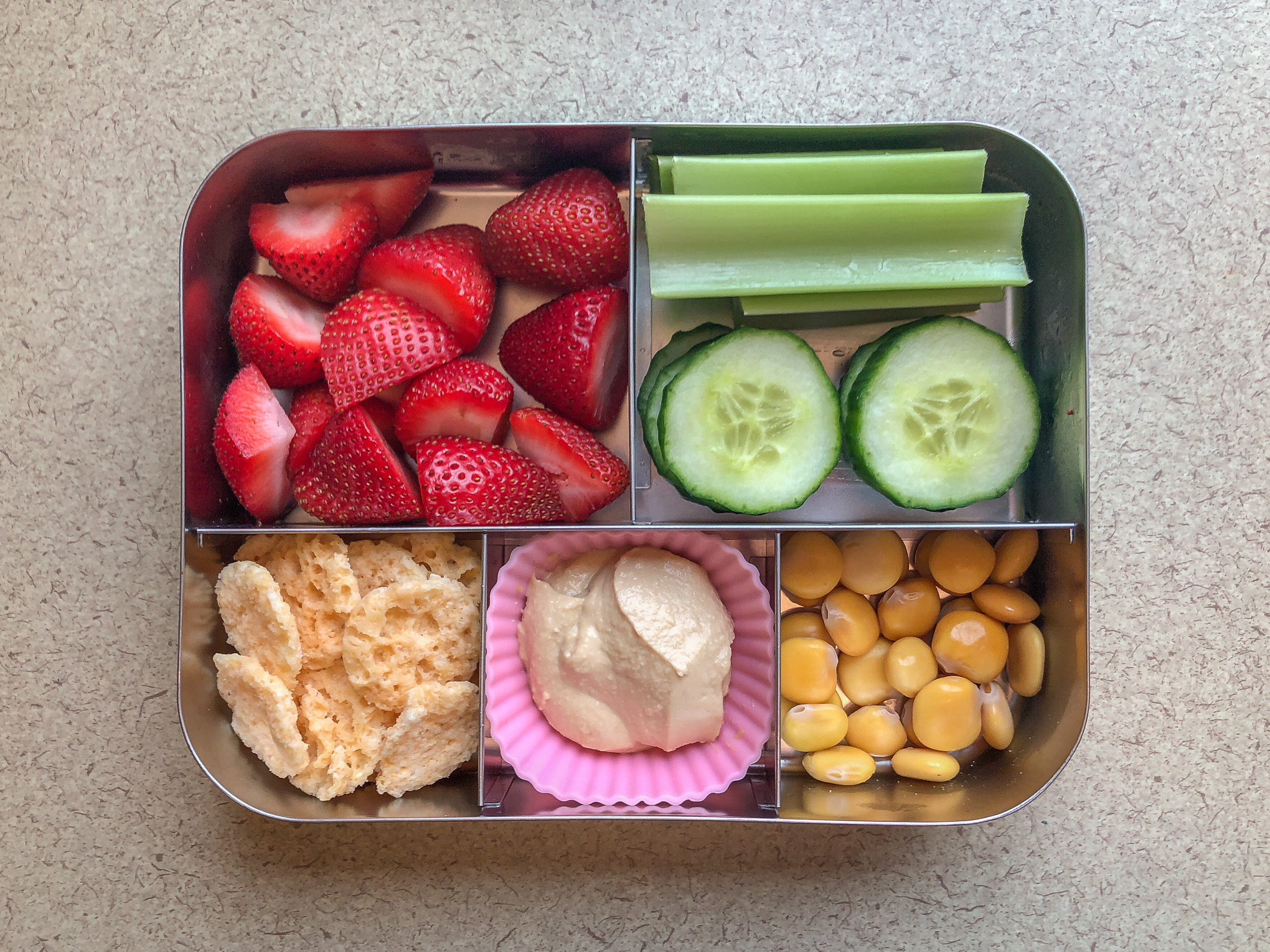 Bento box filled with berries, celery and beans