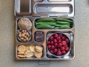 Bento box filled with snap peas, cherries, and pita