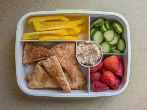 Bento box filled with pita chips and bean dip