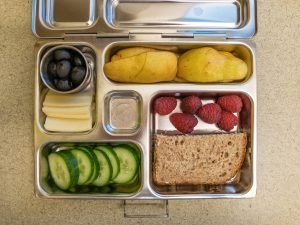 Bento box filled with pear and a sandwich