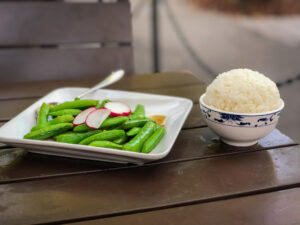 Plate of snap peas and a bowl of white rice