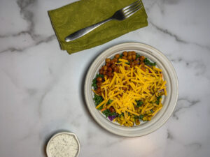 Top down picture of a bowl with beans, cheese and greens