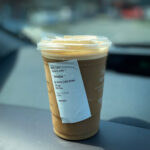 Portrait shot of a cup of iced coffee in focus on a dashboard with a blurred background
