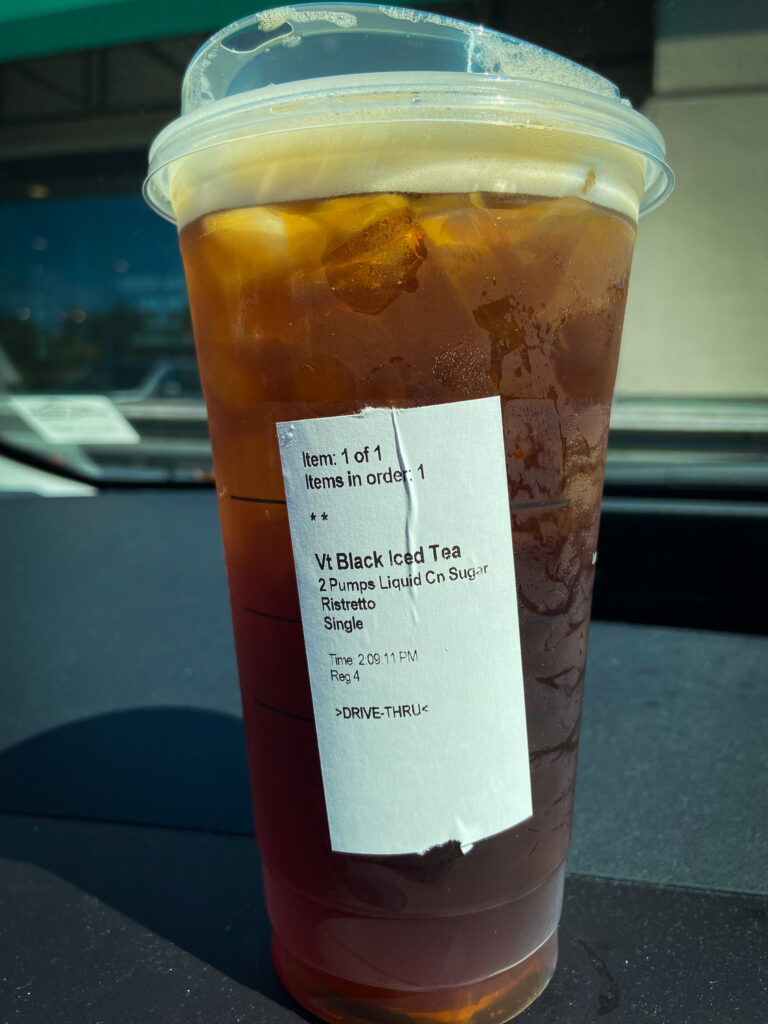 Cup of iced tea on dashboard of car