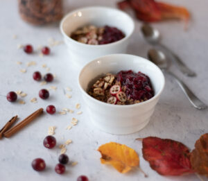 Two bowls of oats and quinoa topped with cranberries and pecans