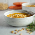 Side view of white marble bowl filled with carrot soup