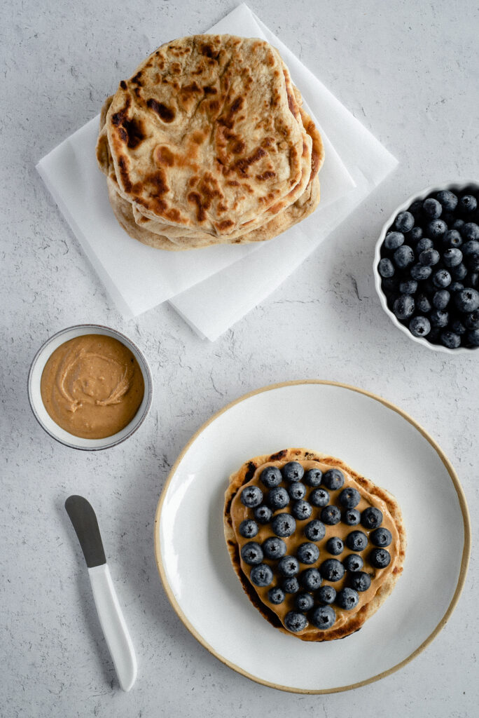 Top down view of naan bread with peanut butter and blueberries
