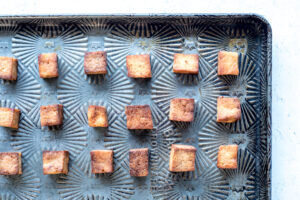 Cubes of baked tofu on a baking sheet