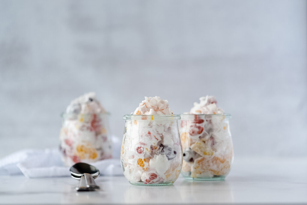Three small jars filled with creamy fruit salad