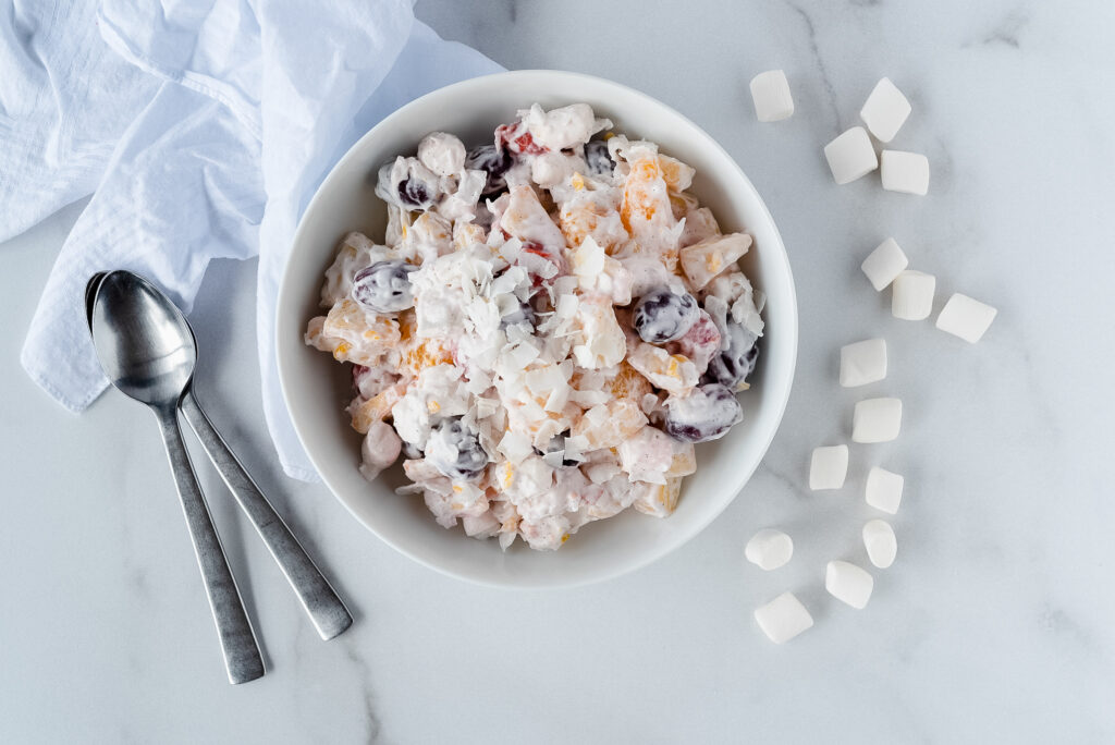 Top down view of a white bowl filled with creamy fruit salad, surrounded by marshmallows
