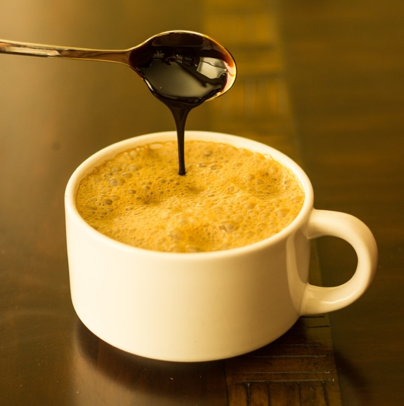 White cup of milk with molasses being drizzled in