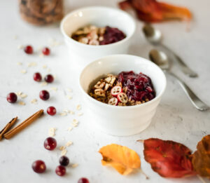 Two bowls of hot cereal surrounded by fall leaves and cinnamon sticks