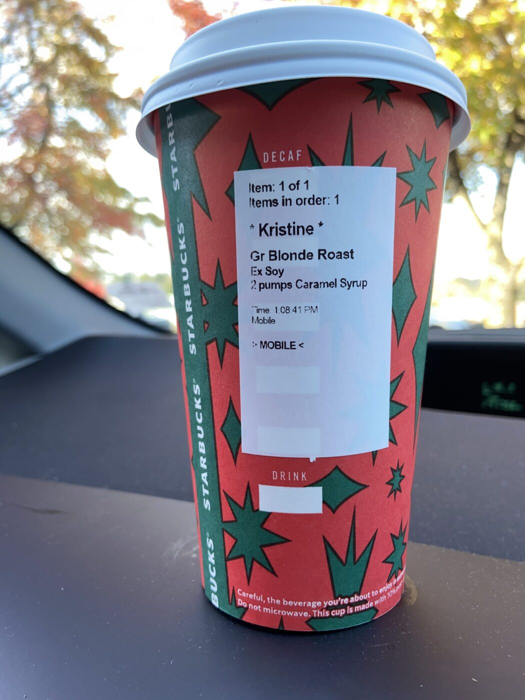 Starbucks cup on a dashboard of a car
