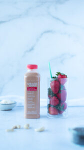 Bottle of smoothie next to glass of berries