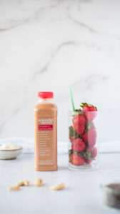 Bottle of smoothie next to glass of strawberries