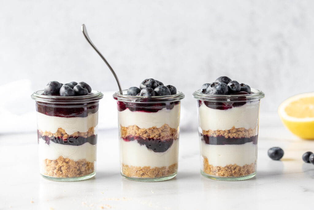 Three jars of blueberry cheesecake with a lemon and blueberries