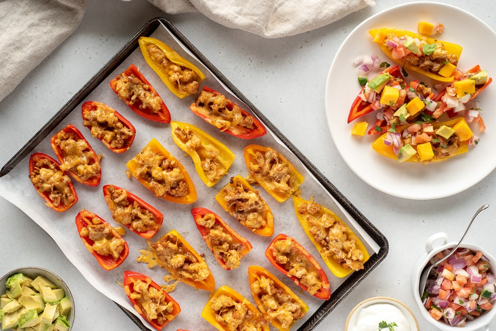 Top down view of a pan of mini pepper nachos next to one serving on a plate