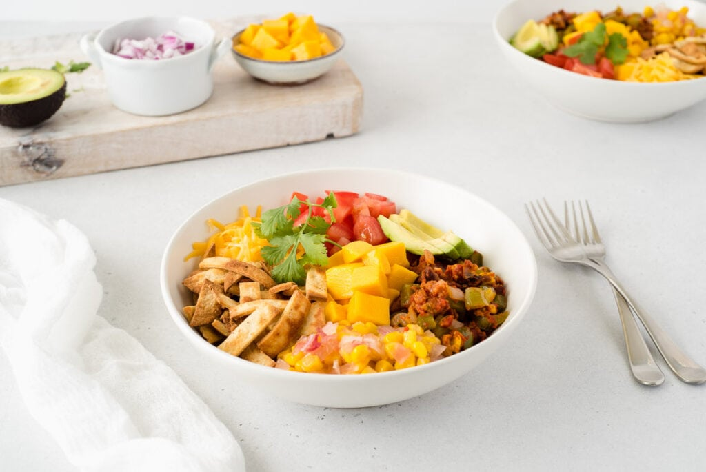 Bowl of taco ingredients next to cutting board