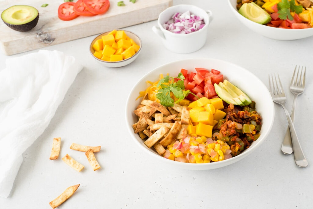 Bowl of taco ingredients surrounded by small bowls of mango, tomato, onion