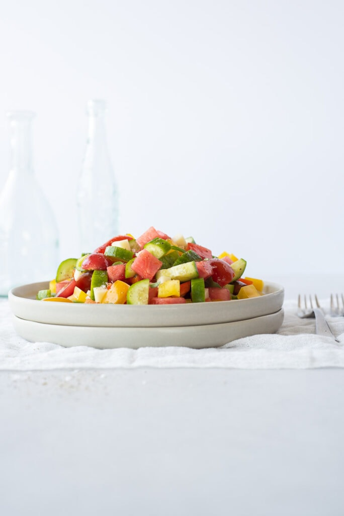 Side view of a plate full of colorful fruit and veggies