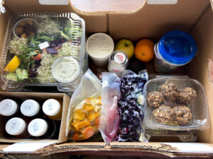 Box filled with juices, smoothie packs and salads