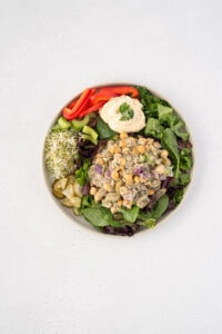Top down view of chickpea tuna salad on a plate with veggies