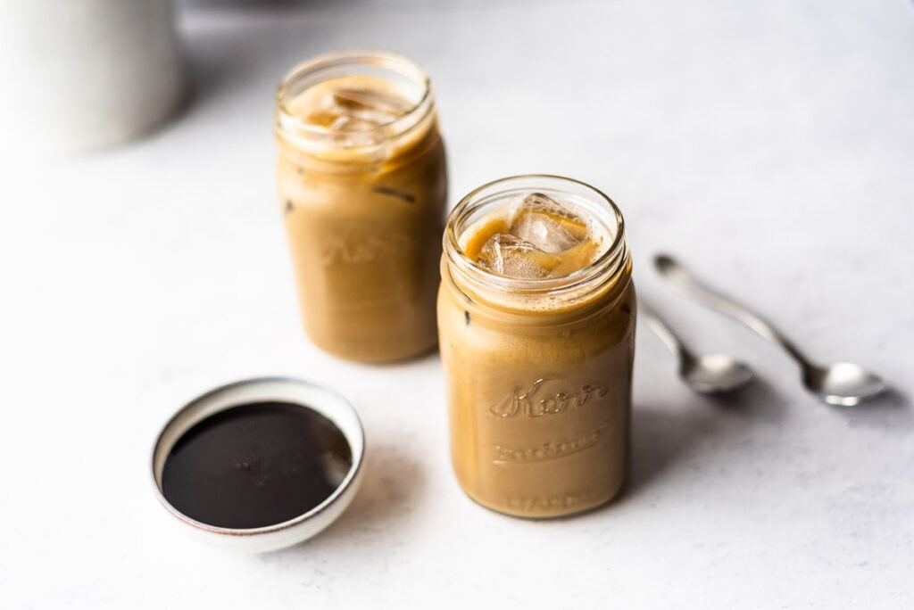 Two jars of molasses milk next to two spoons