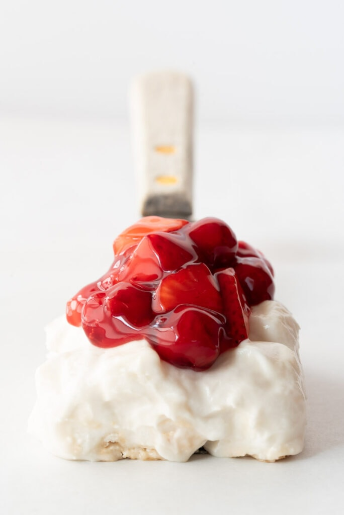 Spatula with one serving of meringue dessert and cherries on it