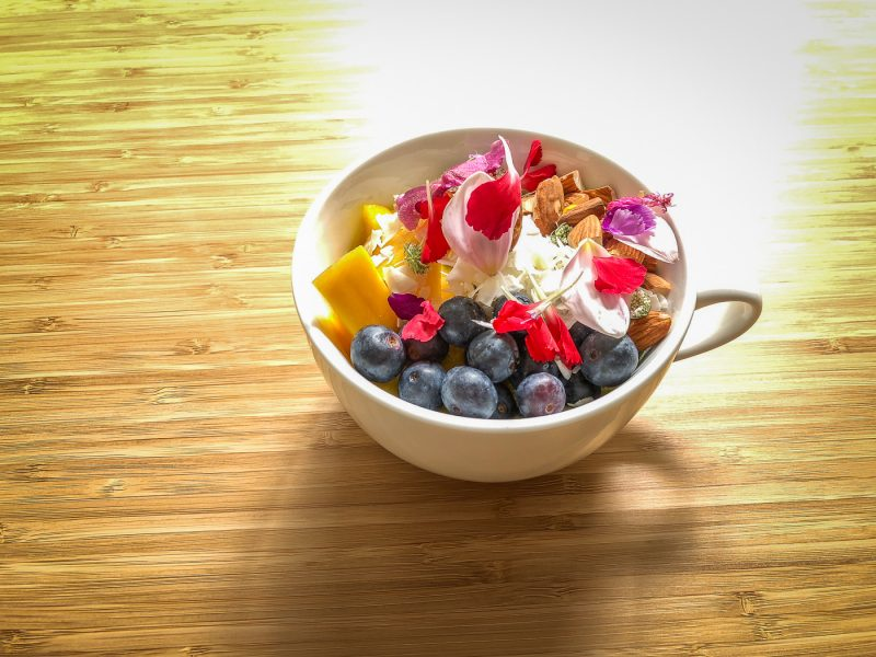 Tea cup filled with fruit, nuts and edible flowers on a table in a ray of sunlight