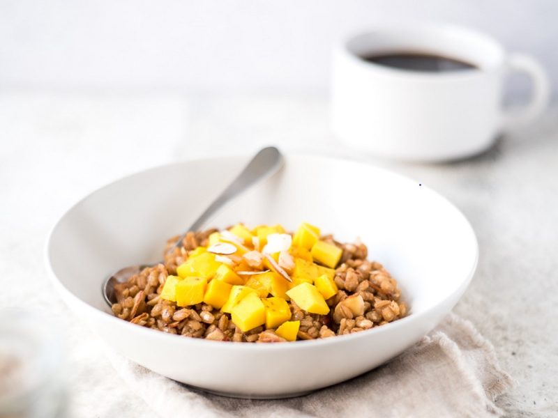 Bowl of cooked barley next to a cup of coffee