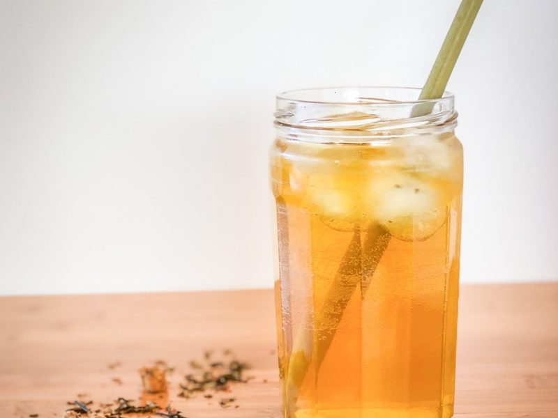 Loose tea on a table next to a glass of iced tea with a straw