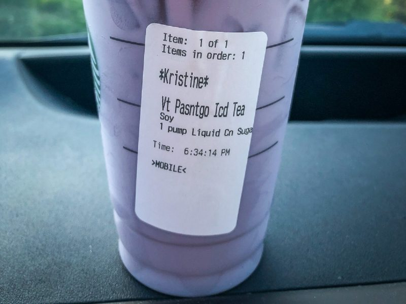 To go cup from Starbucks filled with purple liquid on dashboard of car