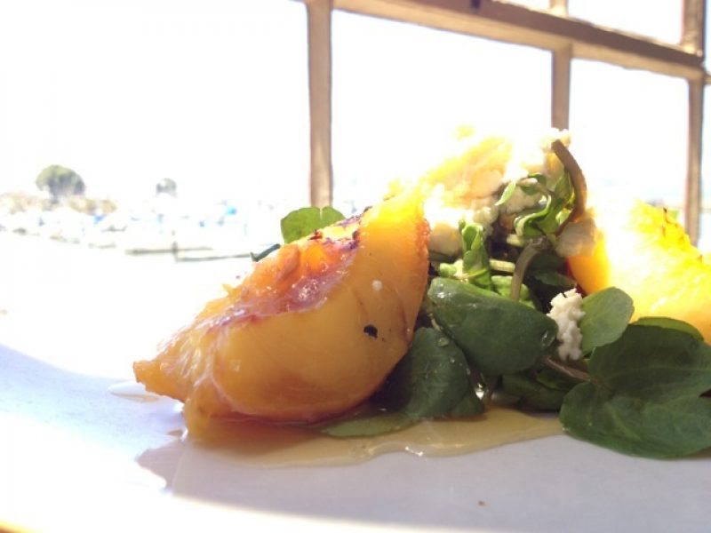 Salad with fresh peaches on a plate