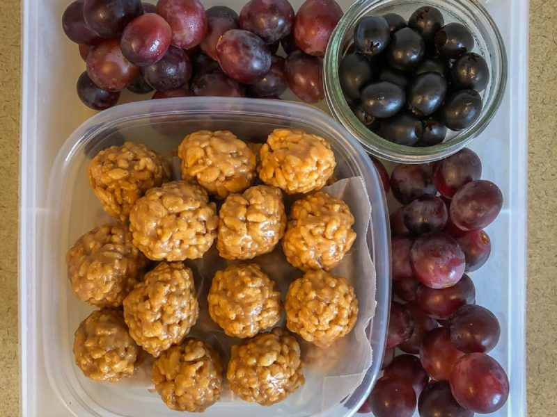 Square tupperware filled with grapes, olives and rice krispie balls
