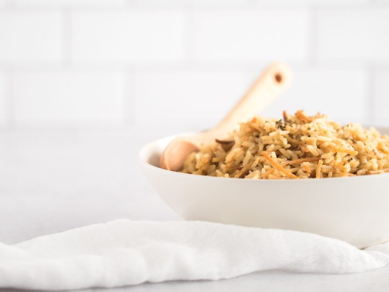 White bowl filled with rice and a spoon