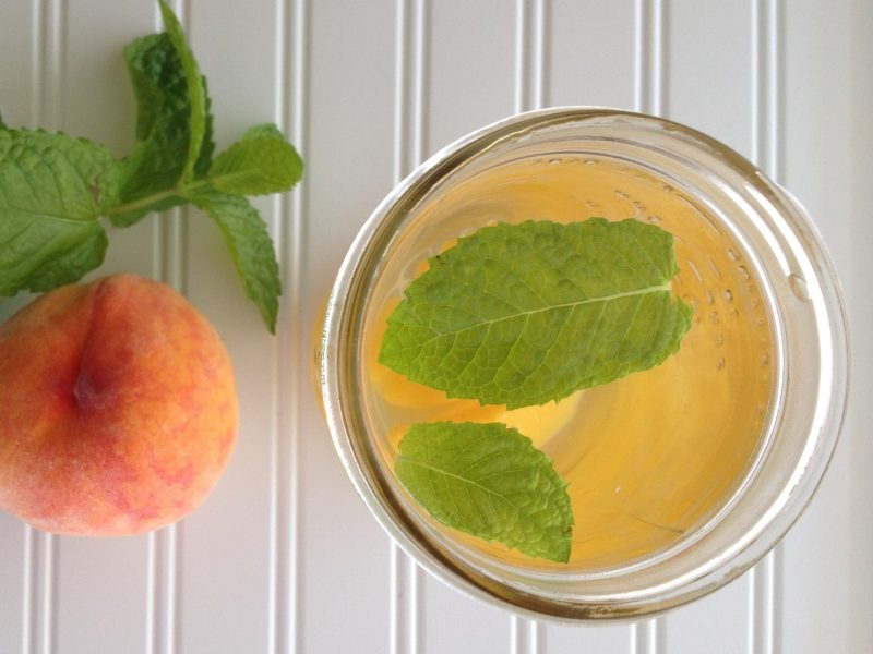 Top down view of canning jar with water flavored with fresh peach and mint leaves