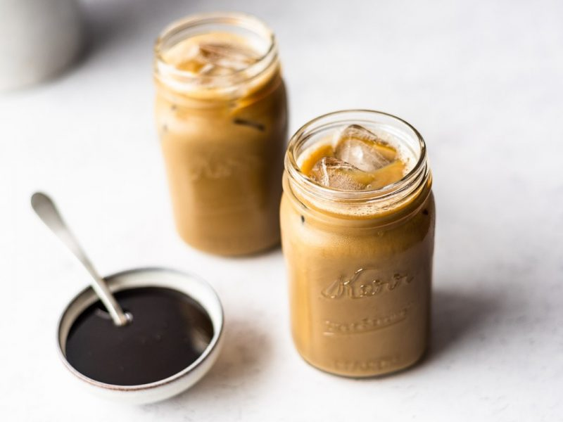 Two jars full of molasses milk next to a bowl of molasses