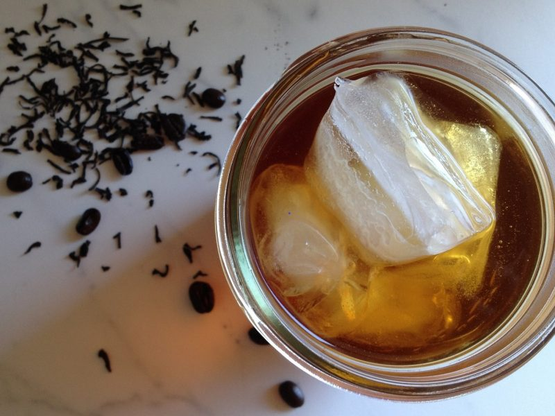 Top down shot of a glass of iced tea and some scattered loose tea