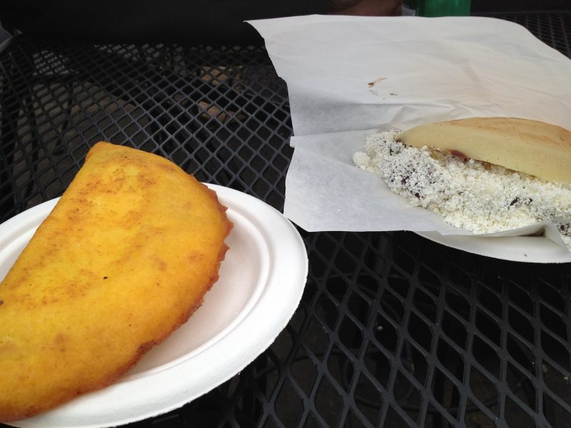 Empanada and Arepa on a paper plate